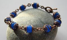 I found these faceted blue jade beads when I was sourcing beads for a commission.  The customer didn't choose these, but I thought they were pretty, and I have no blue in my stash, so I bought them anyway.  With oxidised copper wire.