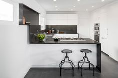 In a kitchen that Brunn built for HGTV in partnership with Bosch, an understated black-and-white palette is paired with a minimal design. The project was named Wrap It Up as an allusion to the film set as well as the way the Caesarstone runs up the wall to create a shelf.