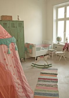 Coral pinks and seafoam green make for a sweet and calming space...no tent, love the rug