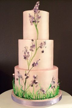 We had a lot of fun creating this celebration cake. It is hand painted with a lavendar pearl finish, hand painted lavendar flowers, 2D sugar petals and 3D sugar flowers. We also added pulled isomalt emerald grass at the bottom – the first time we have used isomalt in this manner.