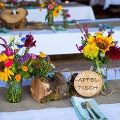 Wunderschöne Tischdeko mit vielen Wiesenblumen. Rustikal und romantisch in toller Kombination. Mit besonderen Tischnamen anstatt einer Tischnummer.