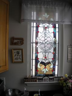 Use of stained glass panel in kitchen sink area to let in light but screen view of neighbor's house.