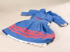 """Kleine """"Blaue Tracht"""", bestehend aus Jacke (blau mit drei silberfarbenen Knöpfen und Manschettenknöpfen an den Ärmeln), Bluse (weiß), Trägerrock (blau mit drei appliizierten umlaufenden roten Streifen, roten Einfassung am Ausschnitt und drei silbernen Knöpfen) , Unterrock mit Hohlsaumstickerei am Saum. Kindertracht Keitum #Sylt"""
