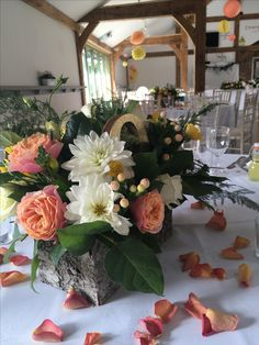 Coral roses, white dahlia and yellow freesia table decoration in bark container.