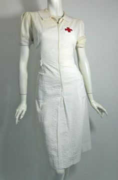 White plisse cotton late 1930s Red Cross nurse uniform. Zip front, red cross at chest, red embroidered bar on sleeve.