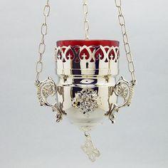 Porta lampada per il Santissimo da appendere. Questa Lampada è realizzata in ottone argentato lucido, contiene il bicchiere in vetro rosso alto 8 cm e catena lunga 85 cm circa.  Ideale per ogni cappella ed adattabile a qualsiasi tabernacolo.