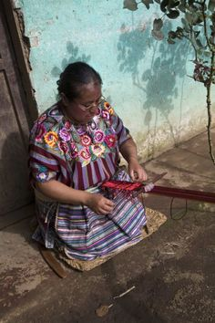 Mujer de la familia Cot tejiendo una faja de cintura con telar de palitos en el patio de su casa en Chuinimachicaj