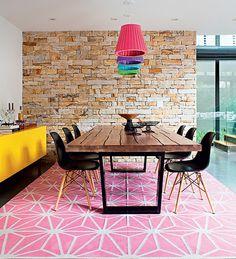 """Tudo tem cor: do tapete rosa aos pendentes, passando pelo móvel amarelo. """"Preferi materiais neutros e escuros, para entrar com cor e estampa na decoração"""", conta a moradora, a estilista Gabriela. Projeto da arquiteta Monica Drucker"""