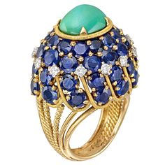 MARCHAK Gem-Set Domed Dress Ring. Gem-set domed dress ring, centering on an oval-shaped cabochon-cut turquoise, surrounded by 49 pavé-set blue sapphires weighing approximately 5.00 total carats, accented by twelve full-cut diamonds weighing approximately 0.30 total carats, mounted in an openwork, polished and twistwire gold setting. Paris. 21st centuty