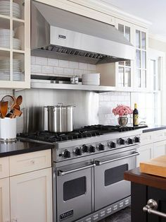 With double ovens and a convenient warming shelf, the new professional-grade range is one of the homeowners' favorite additions. Its location -- just a turn from the island -- allows easy conversation between the cook and guests.