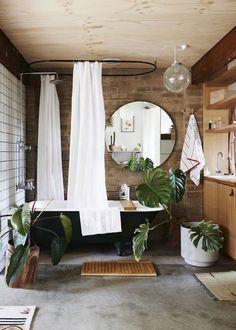 Mur en brique et sol en béton, le brut est la touche tendance de cette salle de bains zen.