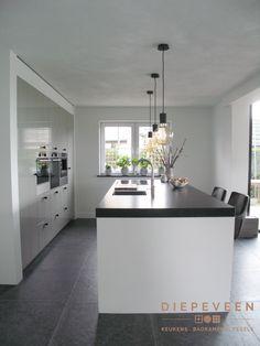 Wat een mooie keuken met een grote kastenwand en een kook en spoel eiland