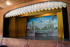 The stage, with backdrop, front-curtains and ruffled, tassled stage curtain drawn up, at the historic Chautauqua Auditorium in Waxahachie, TX.  From the preservation society's website.