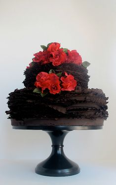 Dark chocolate ruffled cake with red flowers.