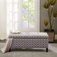This modern storage ottoman accentuated with button tufting provides ample storage and features an elegant grey fretwork fabric with black noir legs.