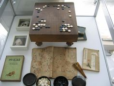 "The ancient Weiqi table with traditional chinese gaming ""Qi"" (stones). To the right there is an ancient Weiqi book (about XVIII century)."