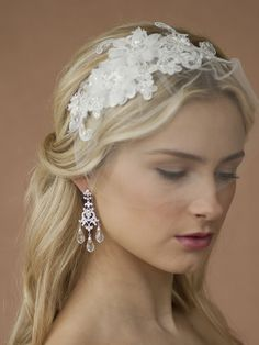 """This luxurious Bridal Headband has a European Lace Applique (8"""" across x 3"""" w) embellished with crystals, pearls, bugle beads & sequins. Our wedding Headband has an alluring 5"""" petite tulle face veil just sweeping the eyes. The satin band is 1/8"""" w. Handmade in the USA, this ethereal floral lace applique headband is set on a slender Ivory satin wrapped metal headband. This enchanting Wedding Headband uses delicate and breathtaking Lace Appliques highlighted by two gorgeous embellished…"""