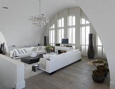 Lichte woonkamer met getoogde shutters. Wat een prachtige ruime en lichte woonkamer is dit! De bijzondere vorm van het plafond wordt door de mooie getoogde shutters nog eens extra benadrukt. Doordat de raambekleding op maat is gemaakt, komen de ramen extra mooi uit. Jasno Shutters