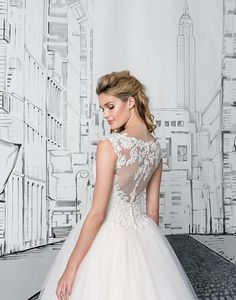 A cathedral length train that bridal dreams are made of. This ball gown features a Queen Anne neckline, heavily adorned bodice, basque waistline, full tulle skirt, and hem lace. Available with the same amount of sophistication but with a 72 inch train as style 8892T72.