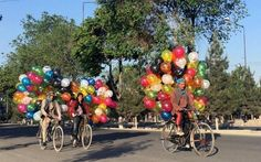 Afghan balloon vendors riding their bicycles, look for customers in Kabul.