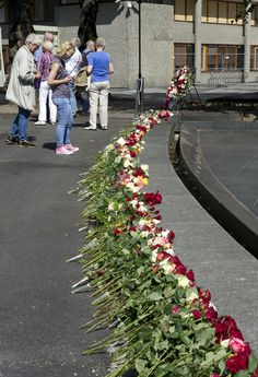 """The image is part of a series that follows the photo documentation was done by the Norwegian Museum photographer, Anne-Lise Reinsfelt, in the aftermath of the terrorist attacks in Oslo and Utøya on 22 July 2011. Her burst """"Grief in the public domain"""" shows the diversity of flowers , candles, poems, photographs, objects and greetings that people leave out in the streets of Oslo. This picture is taken in conjunction with the one-year mark for these events."""