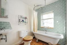 Pale green rectangular tiles; waterfall shower over bath with circular shower rail; aqua?