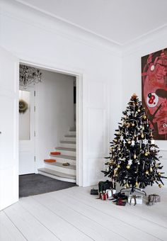 Scandinavian Christmas home with color coded golden ornaments on the christmas tree.