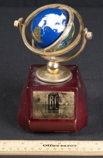 SMALL QUARTZ CLOCK WITH BLUE GLOBE. IT HAS A BISHOPS CIRCLE *SEND ME TO THE NATIONS* PLATE. MEASURES 8 IN. TALL.