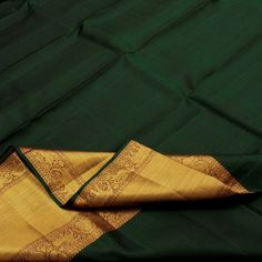 This silk from Sarangi boasts of a bottle green silk body creating its own luster and sheen. The wide gold border is trimmed with a pinch of kumkum and woven yali, annapakshi, horse (Bottle Green Saree) Silk Saree Kanchipuram, Organza Saree, Soft Silk Sarees, Cotton Saree, Green Silk, Pink Silk, Bottle Green Saree, Indiana, Wedding Saree Collection