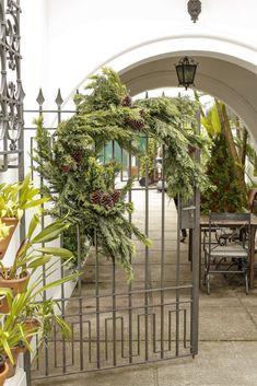 No portão da entrada da casa, para das as boas-vindas ao convidados e entrar no tema de nosso almoço, fixamos duas coroas de tuias com pinhas secas, como se fossem metades de guirlandas, feitas por Marcinho, da Milplantas.