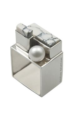 This silver square ring features howlite stones in tonal settings and a single pearl centerpiece