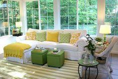 breites wohnzimmer mit großen fenstern und aussicht ins grüne