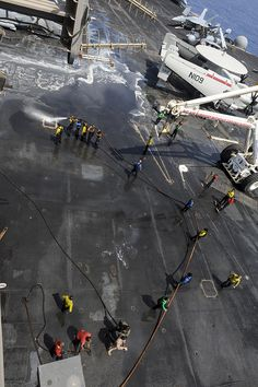 U.S. 5TH FLEET AREA OF RESPONSIBILITY (Sept. 30, 2013) Sailors wash down the flight deck aboard the aircraft carrier USS Nimitz (CVN 68). Nimitz Strike Group is deployed to the U.S. 5th Fleet area of responsibility conducting maritime security operations and theater security cooperation efforts. (U.S. Navy photo by Mass Communication Specialist 3rd Class Phil Ladouceur/Released)