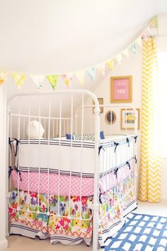 the bunting strung diagonally across the bed, the picture hanging placement, those are my dining room curtains!  should I switch them to the nursery?  the crib sheet and ruffles . . .