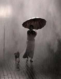 SAUL LEITER Saul uses lighting and other objects to frame his subjects and this is no different - the rain and umbrella frames the woman and her dog. The black and white coloring makes it look eerie and the rain makes it look like a watercolor. Saul Leiter, Walking In The Rain, Singing In The Rain, Dog Walking, Alfred Stieglitz, Rainy Night, Rainy Days, Stormy Night, Street Photography
