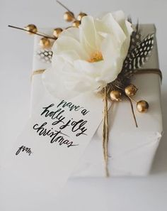 We headed to Pinterest to find beautiful new ways to present your presents. We love this glam version with twine, silk flowers and berries.