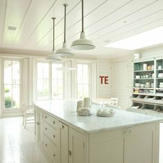 All-white country kitchen.  The muted hue in this kitchen promotes laid-back, casual style. Quirky accessories and furniture, such as the shabby-chic dresser, add personality to the scheme. Dovetailed drawer handles in a metallic finish give this country kitchen a contemporary update. Kitchen units, Plain English.