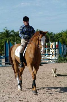 TIP 3: To ask a horse to round, George raises his hand and drives the horse forward from his inside leg to his outside rein. When the horse accepts contact, George softens and lowers his hand.