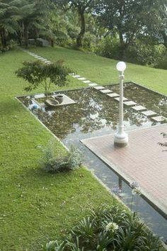 Modern koi pond with pavers backyard inspiration for Modern pond waterfall