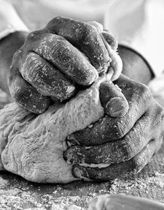 hands kneading dough in black and white