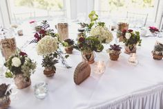 A woodland inspired spring wedding, where we brought the outside 'in' with tree-style centrepieces, wood slices, bark wrapped containers, plenty of trailing foliage, white blooms with a pop of red roses. Hire, flowers & styling by Ava Event Styling. Photographer: Anna Clarke Photography Venue: Somerford Hall, Brewood, Staffordshire, UK.