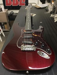 Here's a Legacy Special in Ruby Red Metallic, wood binding, tortoise guard, rosewood board, painted headstock, model logo delete, silver-on-black G&L logo.