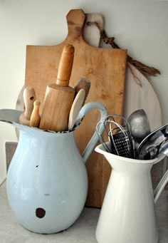 Here, they are stored standing against the wall on the counter.  And vintage pitchers, or new ones, can serve as great organizers in the kitchen.