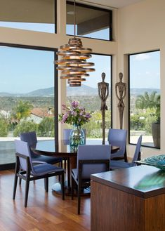 Large+windows+bring+tons+of+natural+light+into+this+contemporary+dining+room.+Blue-gray+chairs+are+paired+with+a+simple,+round+table,+but+the+star+of+the+space+is+the+cylindrical+chandelier.+