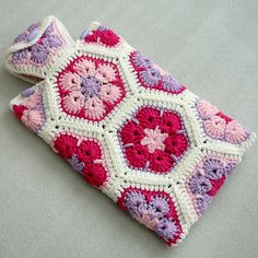 Crochet Hot Water Bottle Cozy African Flower Hot by CrochetbyLilyThis hot water bottle cover is hand crocheted with African flower motifs on both the front and back. Hand made with acrylic yarn in pink, hot pink, light purple, and white colors. Diy Crochet And Knitting, Crochet Crafts, Hand Crochet, Crochet Projects, Crochet African Flowers, Water Bottle Covers, Crochet Phone Cases, Crochet Mobile, Crochet For Beginners Blanket