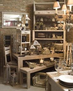 Multi-layers visual merchandising for a shabby chic home decor store. shelving and tables make it easy for customers to see lamps, candle holders etc..