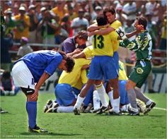 Roberto Baggio hangs his head in dejection after missing Italy's final shot in a shootout in the 1994 World Cup final , giving Brazil the title. Brazilian players celebrate their win in the background