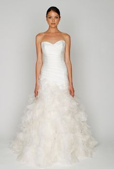 The Monique Lhuillier Bliss 1213 is a silk white organza strapless sweetheart asymmetric draped elongated waist gown with textured circle skirt. Sweetheart neckline, dropped waist, ruffled bottom, tra