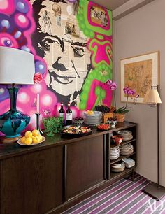 A graffiti-like canvas by Jay Lohmann hangs above the living room's console, which stylist Carlos Mota uses as a server during frequent buffet dinner parties in his New York City residence; the framed work on paper is by Mario Abreu.