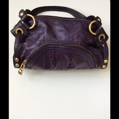 "Leather purse This purple colored purse is full of storage. Gold toned hardware and zippers. One outside zip pocket and one open pocket. Inside holds 2 open pockets with 1 zippered pocket. No shoulder strap. Measures 7"" deep; 12"" across and bottom width is 4"". Like new. Bags"